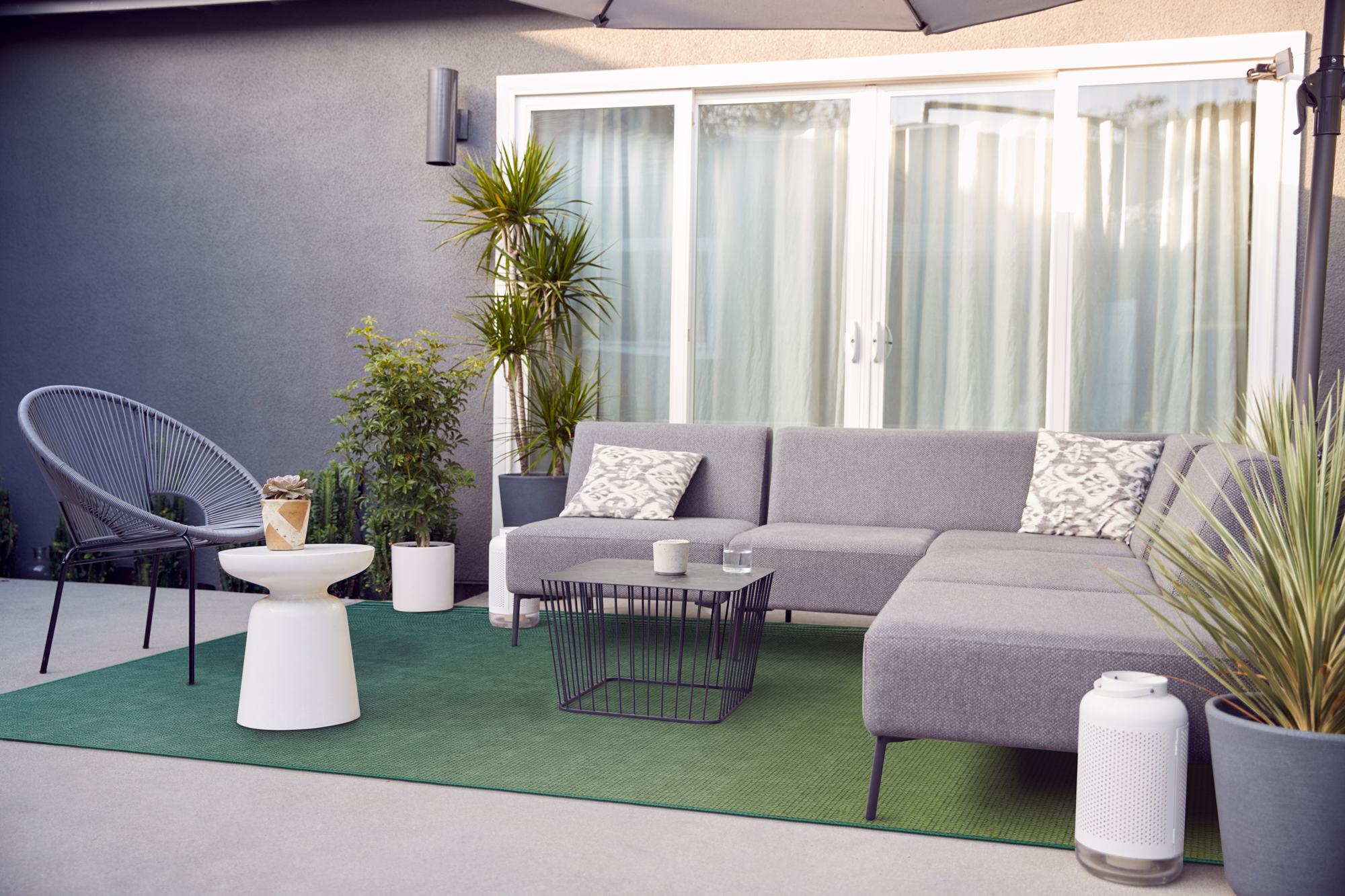 Modern outdoor patio, neutral tones with a vibrant green image impressions rug.